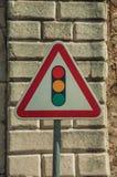 Vägmärke för trafiksignal som framåt är främst av stentegelstenväggen royaltyfri foto