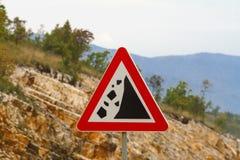 Vägmärke för varningsstennedgång på bergvägen Arkivbild