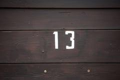 Vägmärke på ett hus som läser numret tretton som målas med vit målarfärg på träpanel Arkivfoton