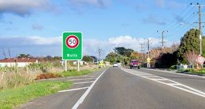 Vägmärke som designerar en femtio kilometer per resande för timmehastighetszon till och med staden av tjurar arkivbilder