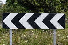 Vägmärke vänster riktning Arkivbild