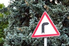 Vägmärken farlig vänd för vägmärke till rätten på bakgrunden av träd arkivfoto