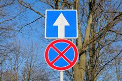 Vägmärken inget stoppa och parkera och en väg Arkivfoto