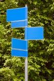 Vägmärken med en gräsplan lämnar bakgrund Royaltyfri Foto