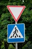 Vägmärken på en bakgrund av träd, ger vägen, övergångsstället, trafikregler, vägteckning royaltyfria bilder