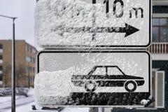 Vägmärken som parkerar på gatan under insnöad vinter royaltyfri fotografi