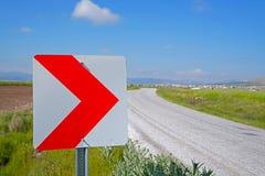 Vägmärken som varnar chaufförer om framåt farlig kurva Arkivfoto