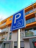 Vägmärkeparkering för folk med handikapp på bakgrunden av ett härligt hem arkivfoto
