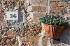 Vägmärket på ett hus som läser numret fjorton, gjorde ut ur metalliska siffror på en marmorgrund royaltyfri foto