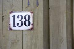 Vägmärket på ett hus som läser numret 138, gjorde ut ur brunt keramiskt Royaltyfria Foton