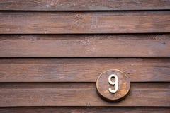 Vägmärket på ett hus som läser numret nio, gjorde ut ur trä Arkivfoto