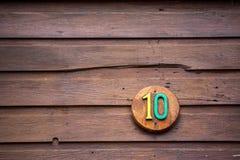 Vägmärket på ett hus som läser numret tio, gjorde ut ur trä Arkivfoton