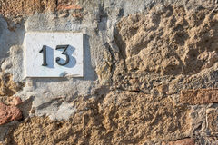 Vägmärket på ett hus som läser numret tretton, gjorde ut ur metalliska siffror på en marmorgrund Fotografering för Bildbyråer