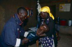 Vägning av en behandla som ett barn på en vårdcentral i Angola. Royaltyfri Fotografi