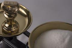 Vägning av socker på jämviktsvåg Arkivfoto