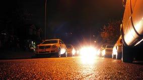 Vägnivåsikt av bilkörning förbi på natten stock video