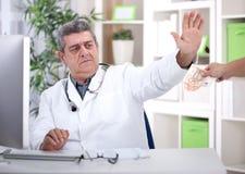 Vägrar den höga doktorn för samvete mutor från patienter Arkivbilder