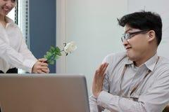 Vägrar den ilskna asiatiska affärsmannen för den mjuka fokusen vita rosor från attraktiv kvinna Besviket förälskelsebegrepp arkivbild