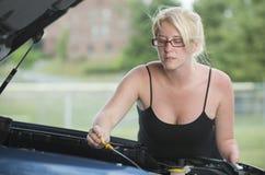 Vägrenhjälp - kvinna som ser under huven av bilen Arkivbild