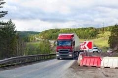 Vägreparation, rött tecken, trafik på en väg, grön skog och bakgrund för molnig himmel arkivfoto