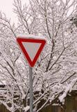 Vägsigne på snöig buskebakgrund Royaltyfria Bilder