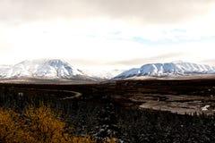Vägspolning till och med den alaskabo dalen med snöig berg Arkivfoton