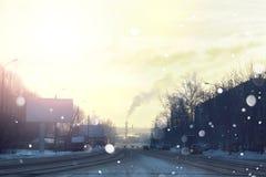 Vägstad med bilen i vintersolnedgång arkivfoto
