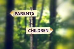 Vägvisare med pilar som itu pekar mitt emot riktningsbarn och föräldrar Royaltyfria Foton