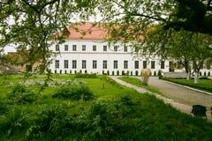 Väl bevarad gammal byggnad med trädgården och gräsplangränden på Dubnoen rockerar i Ukraina Royaltyfri Bild