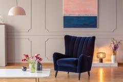 Väl till mods fåtölj i en vardagsruminre med en målning, en hemtrevlig lampa och blommor royaltyfria foton