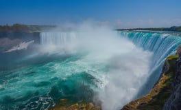 Väldiga Niagara River vrålar över kanten av hästskonedgångarna i Niagara Falls Ontario Dimmig dimmig sprej stiger upp Royaltyfri Bild