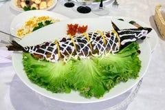 Välfylld fisk på ett uppläggningsfat Table inställningen royaltyfri foto