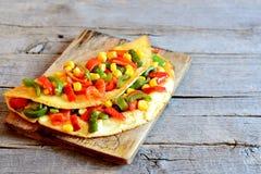 Välfylld grönsakomelett på träbakgrund med det tomma stället för text Stekt omelett som är välfylld med röda och gröna spanska pe Arkivbild