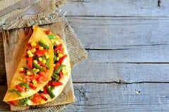 Välfylld omelett för hemlagad grönsak på träbakgrund med kopieringsutrymme för text Äggomelett Royaltyfri Fotografi
