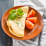 Välfylld omelett med frasig bacon, gröna ärtor och tomaten Arkivfoton
