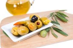 Välfyllda oliv med olivolja och filialen Royaltyfria Bilder