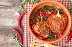 Välfyllda röda peppar med kryddig tomatsås och rosmarin Arkivfoton