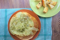 Välfyllt bröd med hönan och den smältta osten på den orange plattan och den röda bruna bakgrunden fotografering för bildbyråer