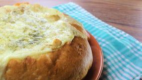 Välfyllt bröd med hönan och den smältta osten på den orange plattan och den röda bruna bakgrunden arkivfoto