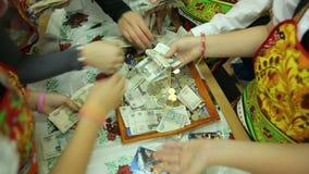 Välgörenhetmässan, en folkmassa av barn räknar pengar arkivfilmer