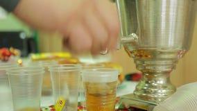 Välgörenhetmässan, häller te in i koppar från en samovar arkivfilmer