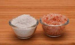 Välj ditt salt - Himalayan eller vagga salt (sidosikten) på trä Arkivbilder