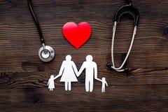 Välj familjsjukförsäkring Stetoskop, pappers- hjärta och kontur av familjen på bästa sikt för mörk träbakgrund Royaltyfria Foton