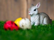 Välj fokusen av kanin som förläggas på grönt gräs framme av kanin ha färgrika en easter ägg Baksidan är en brun wood ram _ Arkivfoton
