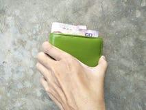 Välj upp en plånbok på golvet Arkivfoto