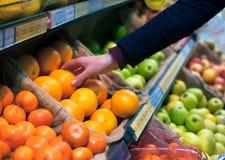 Välja en apelsin i livsmedelsbutik royaltyfri bild