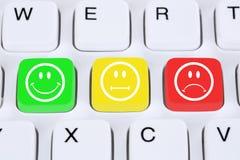 Välja kundtjänstkvalitet med smiley på datorkeyboa Arkivfoto