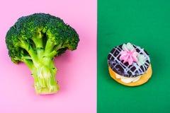 Välja mellan broccoli och sjuklig mat, kakabuske Begrepp av vegetarianism och den sunda livsstilen Royaltyfri Bild
