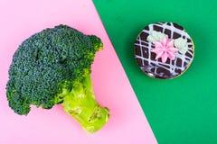 Välja mellan broccoli och sjuklig mat, kakabuske Begrepp av vegetarianism och den sunda livsstilen Arkivfoto
