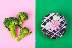 Välja mellan broccoli och sjuklig mat, kakabuske Begrepp av vegetarianism och den sunda livsstilen Fotografering för Bildbyråer